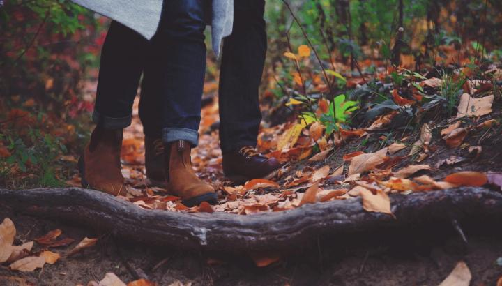 Feet and lower legs of two people standing on forest ground